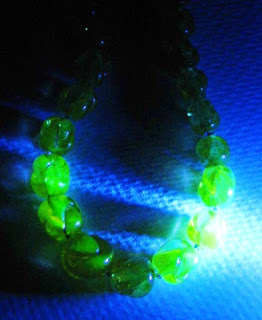 A Uranium glass bead necklace under UV light.
