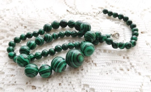 FAKE: this graduated bead necklace has unnatural banding, and the green colours are just too 'off' for malachite. It's also much lighter than the genuine gemstone, which is ice cold and very heavy for its size