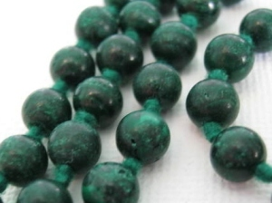 REAL: These are very old vintage malachites, very dark green, very heavy, and knotted in between for security (in fact knotting can be a good (but not 100%) sign of genuine gemstones, as knotting is a laborious process and it's not particularly cost effective to do it on faux stones.