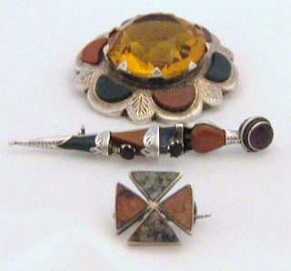 A collection of old Scottish agate jewellery. From top: a vintage 1970s brooch with huge yellow centre stone, a 1920s silver dirk pin in the shape of a tiny dagger, and a tiny early Victorian cross brooch.