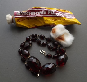 Using Simichrome polish to positively identify an Art Deco Cherry amber colour Bakelite necklace. Simichrome paste is actually pink, but rub it on Bakelite and it will turn the pink paste a yellow colour (varies from mustard yellow to pinky-yellow).
