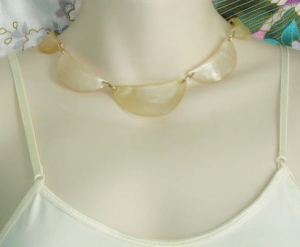 Vintage faux mother of pearl collar necklace, made with crescents of shimmering Lucite panels.